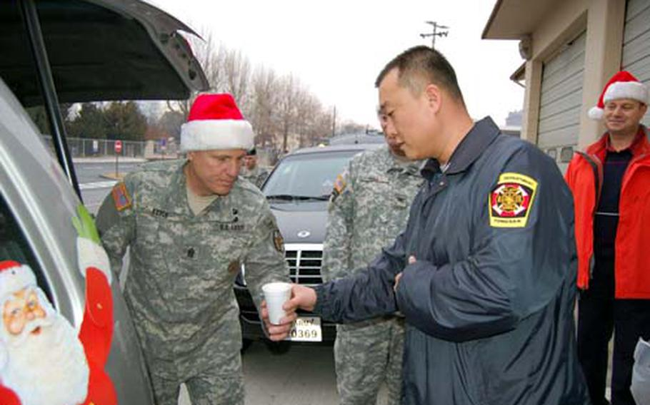 U.S. Army Garrison Yongsan Command Sgt. Maj. Ralph Rusch hands a cup of hot cocoa to Yongsan firefighter Chong Song-uk on Wednesday as part of Operation Santa Express, a 10-year garrison tradition in which officials bring treats to emergency services personnel.