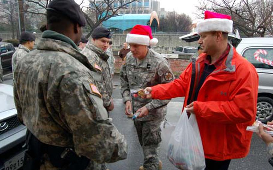 U.S. Army Garrison Yongsan director of emergency services Ricky Oxendine (right) and USAGY Command Sgt. Maj. Ralph Rusch hand out bags of candy to military police at Yongsan Garrison Wednesday as part of Operation Santa Express, a 10-year garrison tradition in which officials bring treats to emergency services personnel.