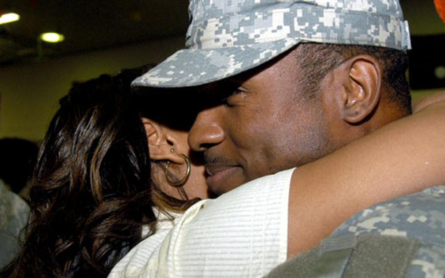 Kishara Allen hugs her husband, Spc. Lacy Thompson Jr., who returned from Iraq on Christmas Day. Thursday also marked the first time Thompson saw his 6-month-old son, Lathan Thompson.