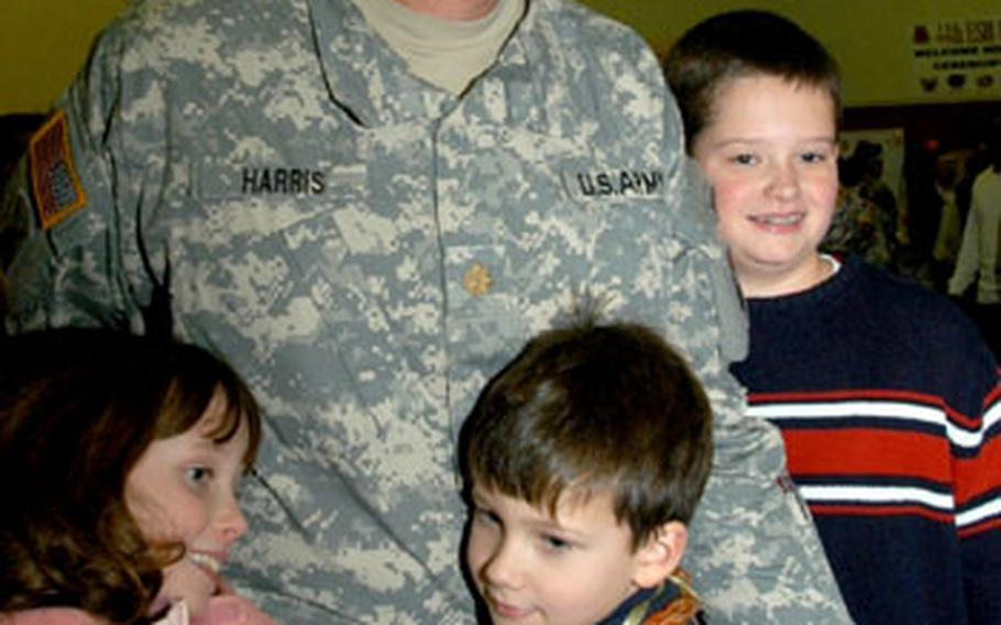 Maj. John Harris' kids crowd around him, with 7-year-old Jack and 11-year-old Catherine hanging on to his legs.