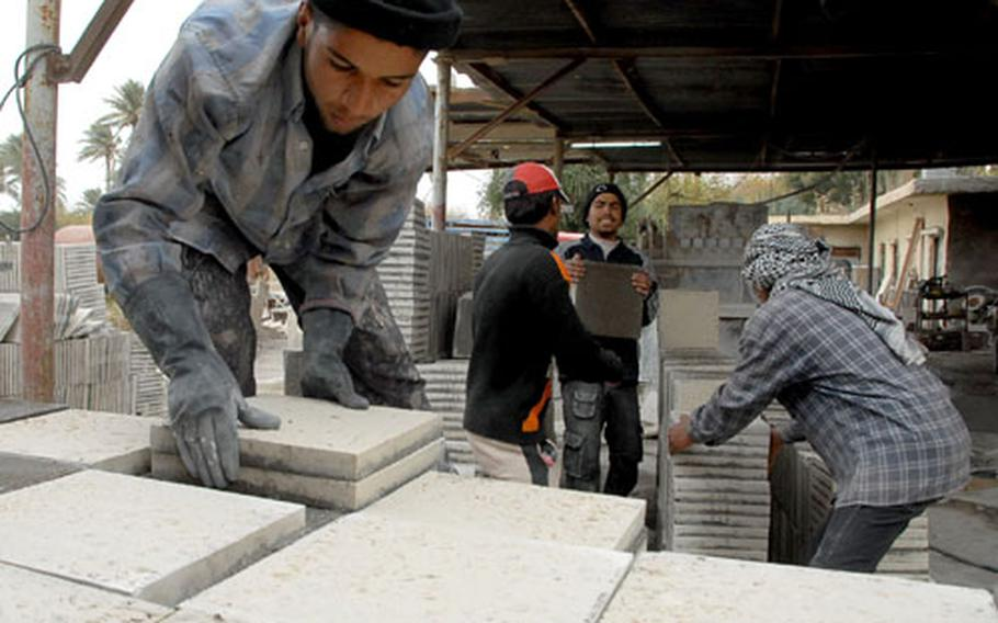 Workers load tile at Moayed Yassin Hassan al-Janabi's factory in Warij on Monday.