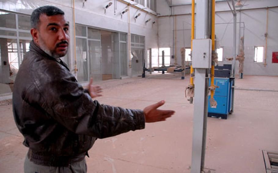 Moayed Saqbani shows the Nissan distribution center he has helped guard since 2003. The facility now could open within months, part of a push to revitalize the Warij industrial district south of Baghdad.
