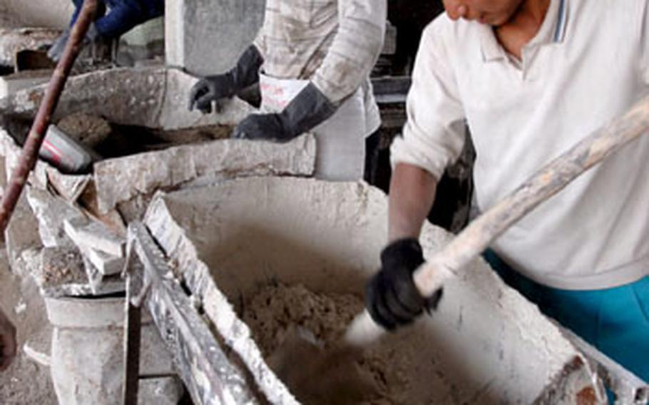 Workers make mix for tiles on Monday at a family-run factory in the Warij industrial district south of Baghdad.