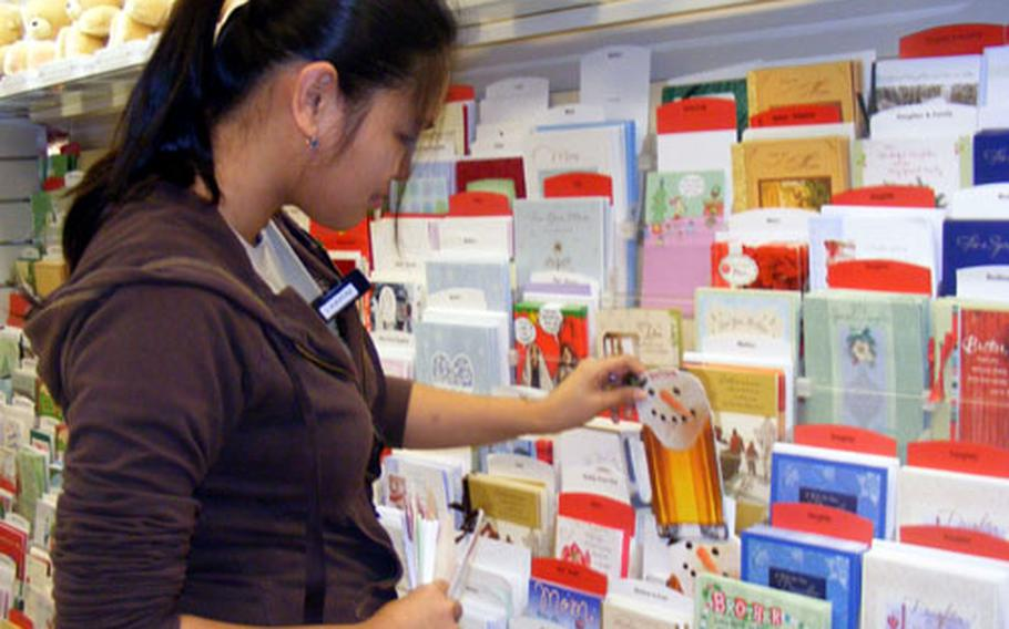 Hallmark Cards representaive Laarni Ruiz removes Christmas cards from the shelves of the AAFES store on Kadena Air Base Friday, making room for the next seasonal card selection.