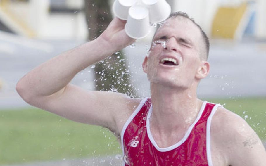 Cpl. Thomas Kunish cools off during the 18th Annual Camp Kinser Open Half Marathon Oct. 7. Kunish finished first overall with a time of 1:17:36, averaging less than six minutes per mile.