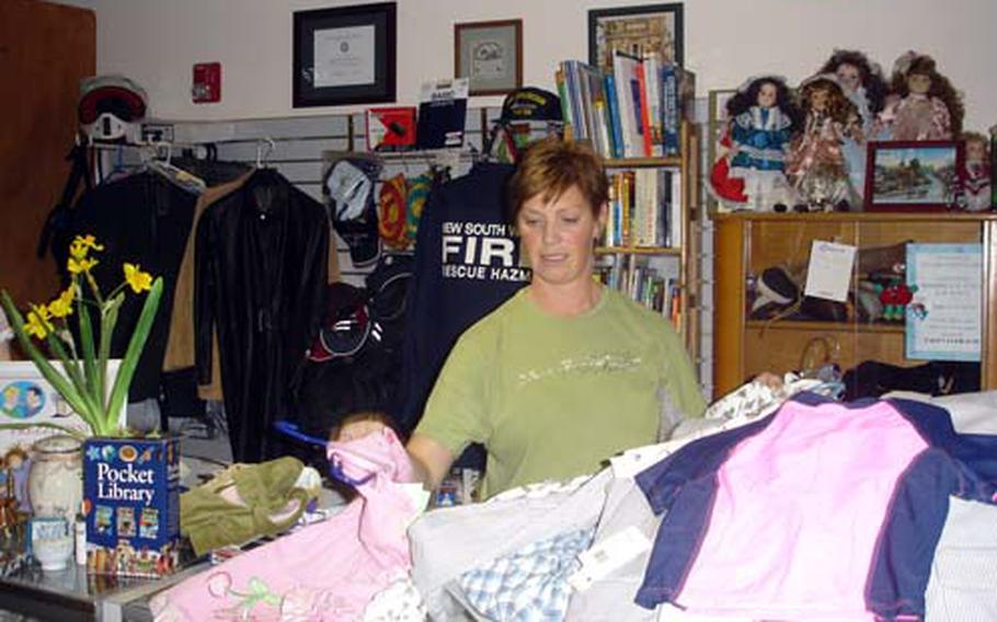 Holly Yager, a volunteer at Forgotten Treasures thrift shop, sorts through donations that will either be sold at the store or sent to charities in Naples and Iraq.