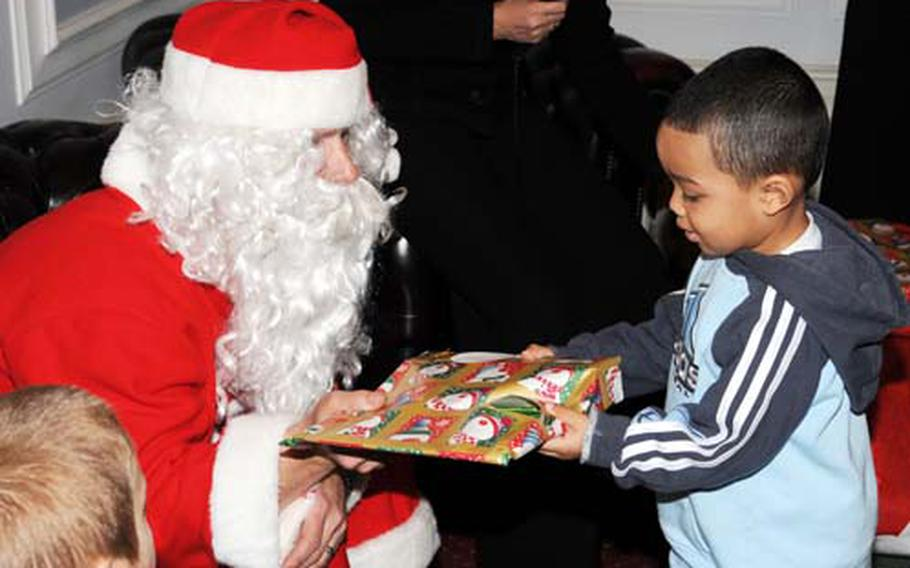 Three-year-old Kaidan Fleshman, son of Staff Sgt. Jerry Fleshman from the 100th Public Affairs Office, accepts a gift from Santa during the deployed spouses' luncheon Dec. 7 at RAF Marham, England. Santa made a special appearance to hand out gifts.