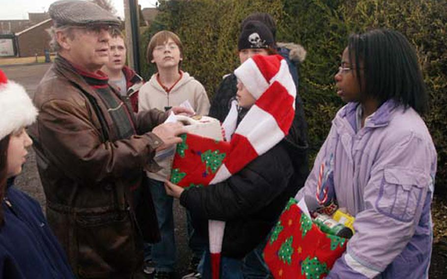 Science teacher Ted Berkey directs a group of Lakenheath Middle School students who made up this year's Polar Express. The sixth-graders delivered canned goods and other household items to elderly residents of Feltwell.