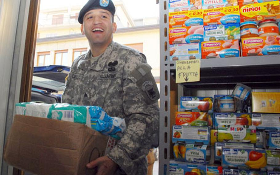 Sgt. Sergio Carillo, 27, of Los Angeles, a Southern European Task Force chaplain assistant, carries donated items into a Vicenza, Italy, food pantry run by the local Catholic archdiocese. Soldiers and families in the Vicenza military community collected food, baby formula and other items for a local charity in Vicenza.
