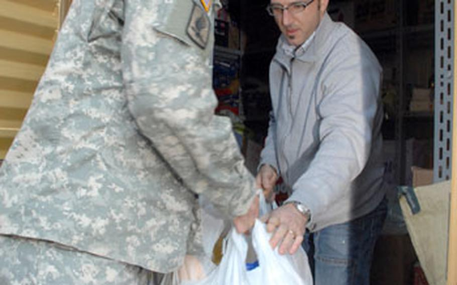 Carillo hands bags of donated supplies to Vicenzo Vario, who oversees a Vicenza, Italy food pantry run by the local Catholic archdiocese.