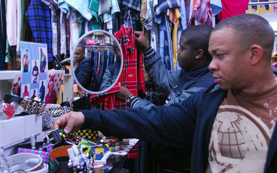 Seaman Orvin McLean, left, 23, of New York City, and Petty Officer 2nd Class Class Ronald Williams, 38, of Miami, Fla., shop for clothes in Sasebo, Japan, on Friday during a port call by the aircraft carrier USS John C. Stennis.