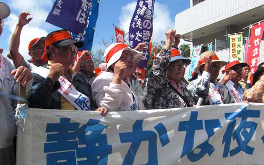 About 100 residents and their supporters Friday rally outside Fukuoka High Court in Naha, Okinawa, while waiting for a ruling of their eight-year long litigation. In 2000, 5,542 residents living in communities surrounding Kadena Air Base sued the Japanese government in an effort to halt flight operations at the air base between 7 p.m. and 7 a.m. and sought $59.5 million compensation.