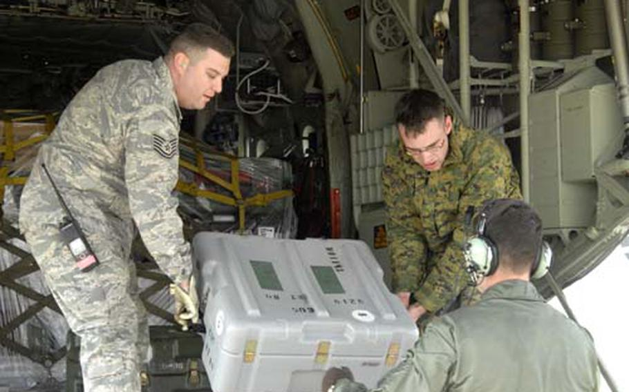Tech. Sgt. Anthony Luddon, 8th Logistics Readiness Squadron, and Lance Cpl. Brendon Shaugnessy, Combat Logistics Regiment 37, hand cargo to a crewmember from a C-130 Hercules on Monday at Kunsan Air Base, South Korea. The Marines, from Marine Corps Air Station Futenma in Okinawa, are at Kunsan for the upcoming exercise Key Resolve/Foal Eagle. Their arrival gave airmen at Kunsan a chance to practice accepting wartime forces, a key component in the Wolf Pack mission.
