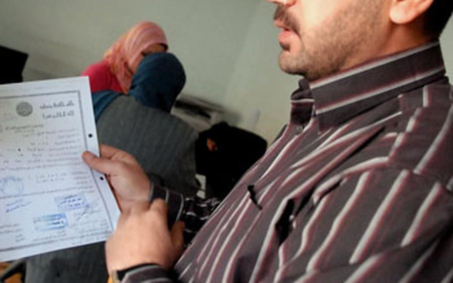 Achmet Hussein, a Mansour District Council employee who helps displaced people return home shows off the paperwork that allows those who fled Iraq's sectarian fighting to get help returning home. Jobs like these could generate popular support for the American-created district and neighborhood councils.