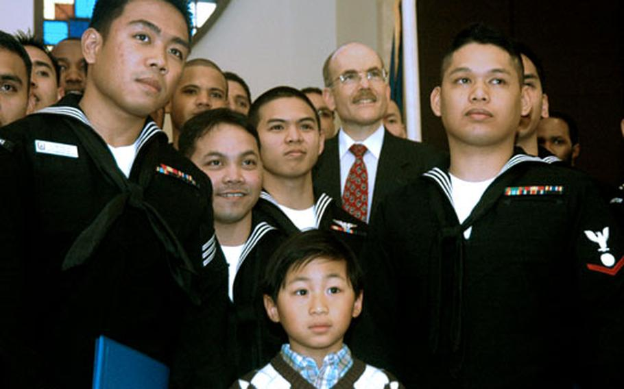 Martin Ulsano poses with servicemembers and spouses who received their certificates of naturalization. Also in the group is U.S. Embassy Charge d'Affaires James P. Zumwalt.