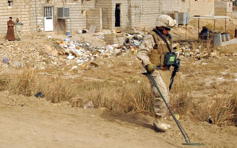 Lance Cpl. Erik Santos sweeps the side of a road for hidden weapons during a cache sweep in Ramadi.