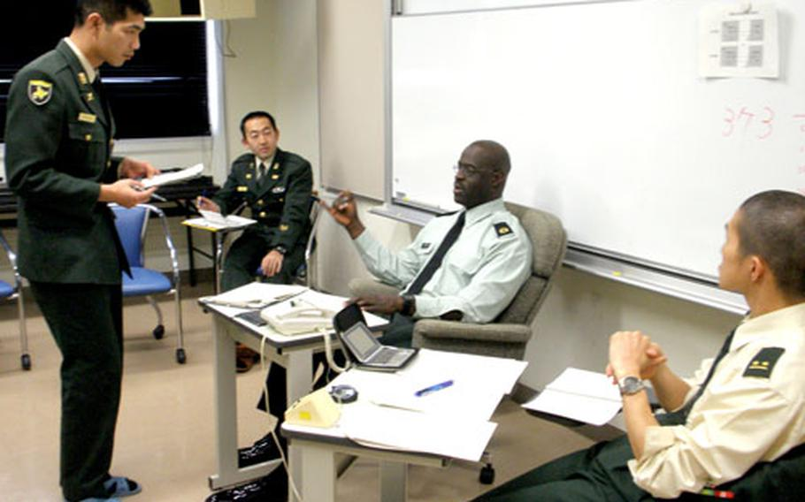 Master Sgt. Frederick Moore gives English language tips to a member of the Japan Ground Self-Defense Force last month at Camp Kodaira.