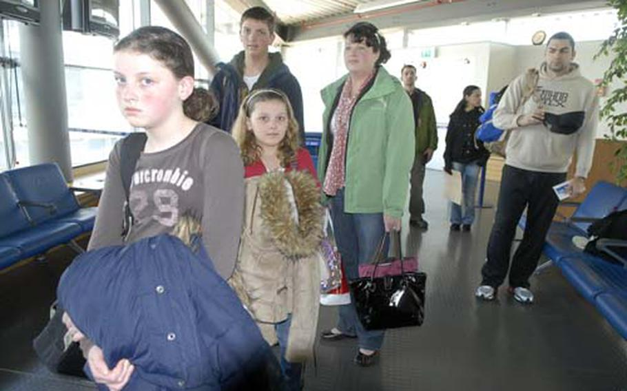 Space-available travelers from Aviano, Lee family members wait in line recently to go through a security check before boarding a flight from Ramstein Air Base, Germany, to Dover Air Force Base in Delaware.
