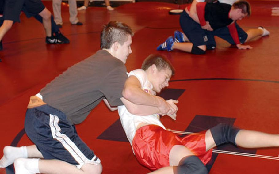Lakenheath High School sophomore wrestler Brandon Searle (in red trunks) squares off with Daniel Carroll at a practice in 2008. Searle is a valued member of the squad, but this will be his last year with the Lancers.