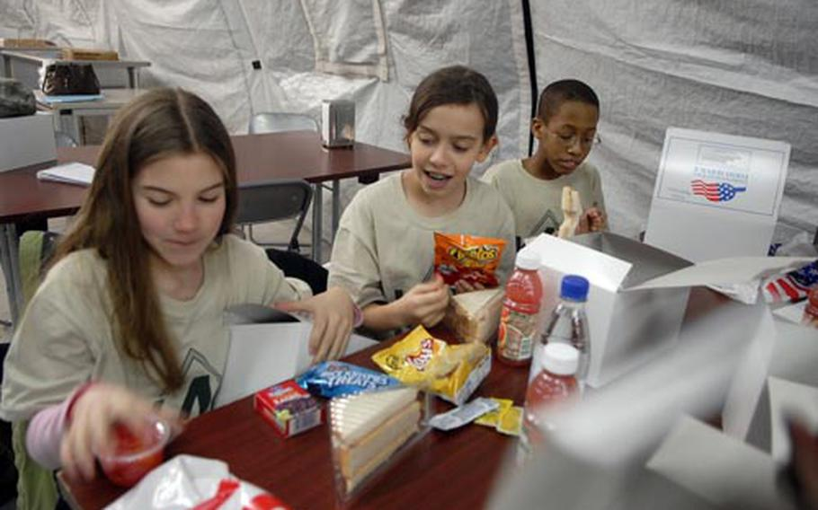 Meals, Ready to Eat weren't on the menu for the Kids4Kids' mock pre-deployment event at the 86th Construction and Training Squadron near Ramstein Air Base, Germany. Ramstein Intermediate School fifth graders Brynley Lacy, Kayla Sriver, and Derek Mattis (left to right) eagerly dug into big box lunches, though they did get to experience eating in a dining hall tent.
