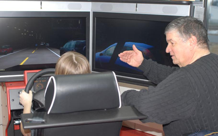 Driving instructor Jim Mollo gives advice to a student using a driving simulator at Grafenwöhr, Germany, on Wednesday.