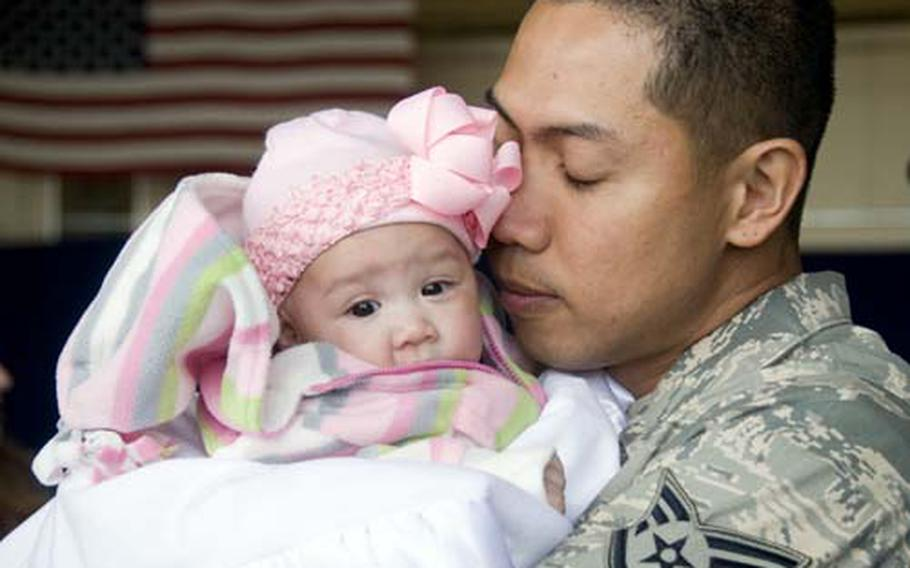 Staff Sgt. Dennis Horlador embraces his newborn daughter, Natyala, for the first time Sunday at Misawa Air Base, Japan, after he returned from a deployment to Iraq.