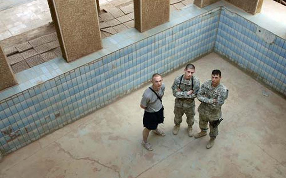 Pfc. Sean Morgan, Spc. Paul Eliss and Staff Sgt. Charles McMahan, left to right, soldiers assigned to Company B, 1st Battalion, 35th Armored Regiment, pose for a photo inside the pool they hope to get working before the three digit heat shows up Friday at Combat Outpost Dolby, Iraq.