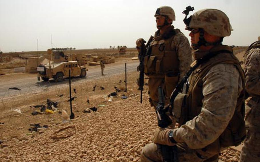 Lt. Col. Thad Trapp, commander of 2nd Battalion, 9th Marines, left, and Capt. Dallas Shaw, right, examine the exterior of Adalla, at joint security station on the outskirts of Ramadi. They hoped to find ways to improve security at the compound.