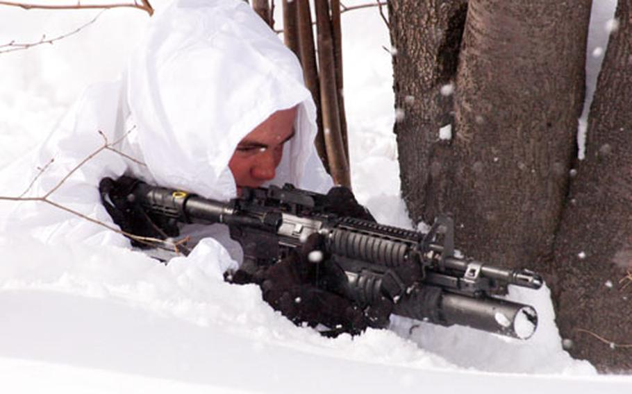 Pfc. Chris Sons plants himself in the snow during sniper training.