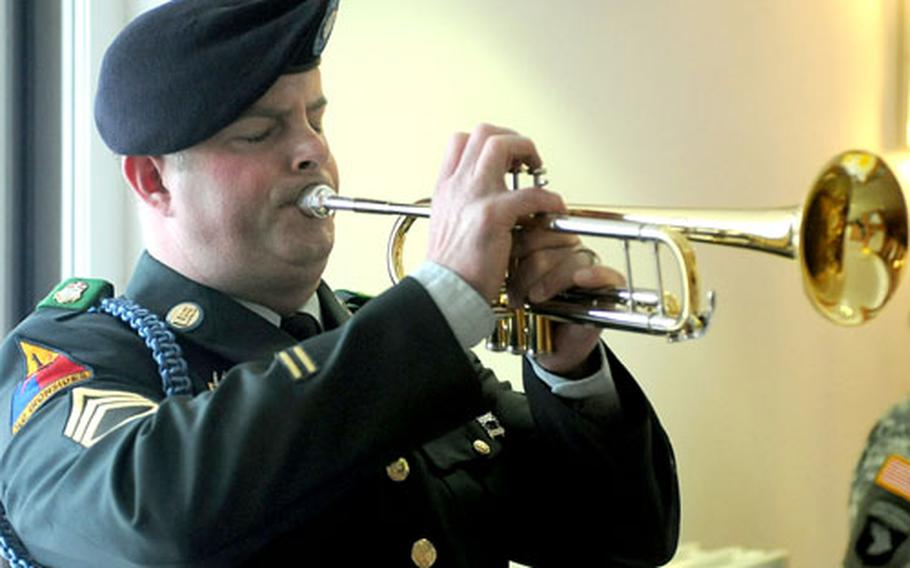 Staff Sgt. Karl Skelton plays taps at the conclusion of the memorial service.