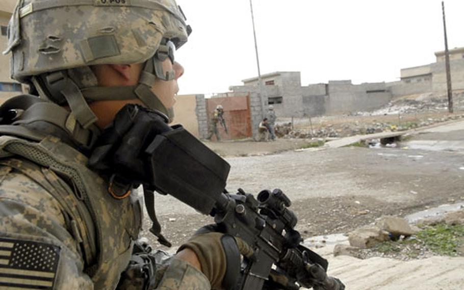 A U.S. soldier peeks out from behind a wall during a recent gunfight in Mosul.