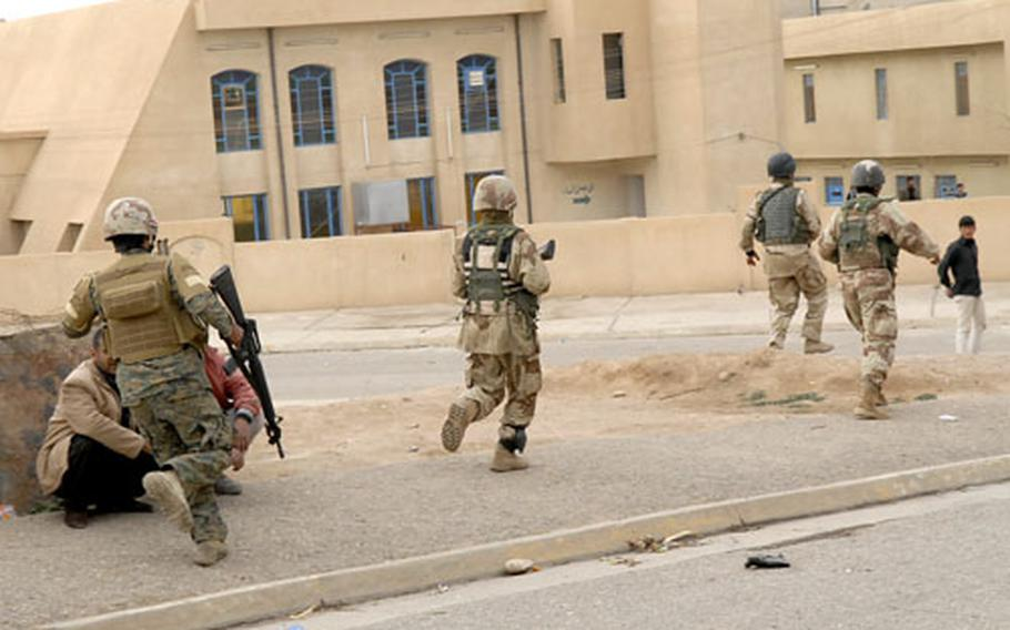 Iraqi soldiers run for cover while under fire in Mosul's Saddam neighborhood.