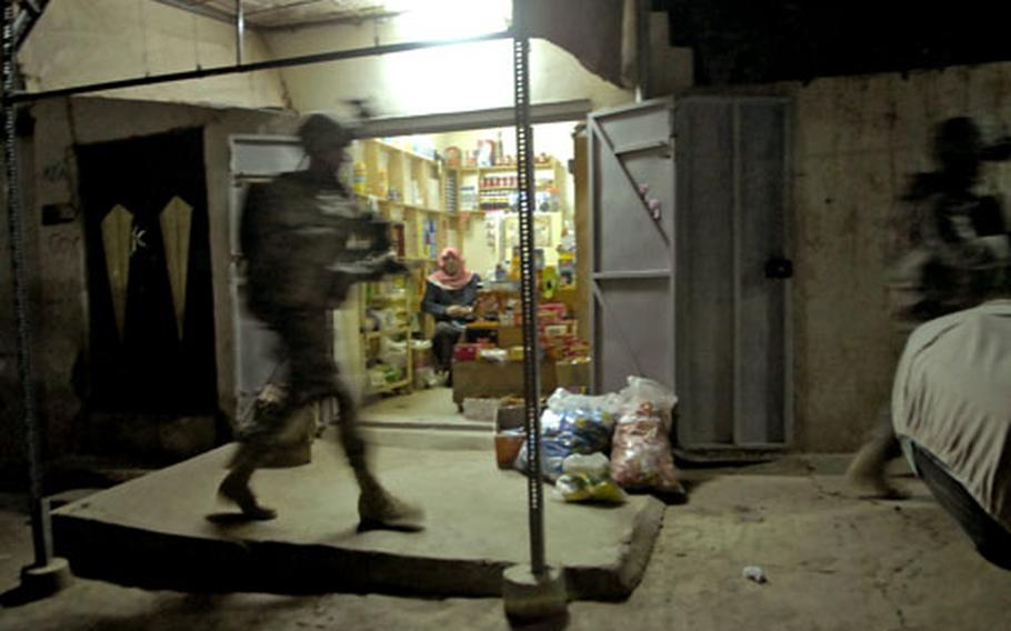 A U.S. soldier passes a shop during a night patrol in Mosul.
