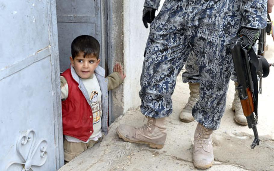 An Iraqi child peeks out at a joint patrol of Iraqi National Police and U.S. soldiers in Mosul.