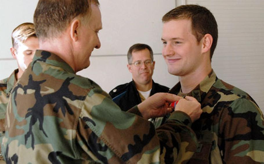 """Navy Capt. James """"Red"""" Smith, commander of Naval Expeditionary Task Force Europe and Africa, Combined Task Force 68, presents a second Bronze Star to Petty Officer 1st Class Adam Miller."""