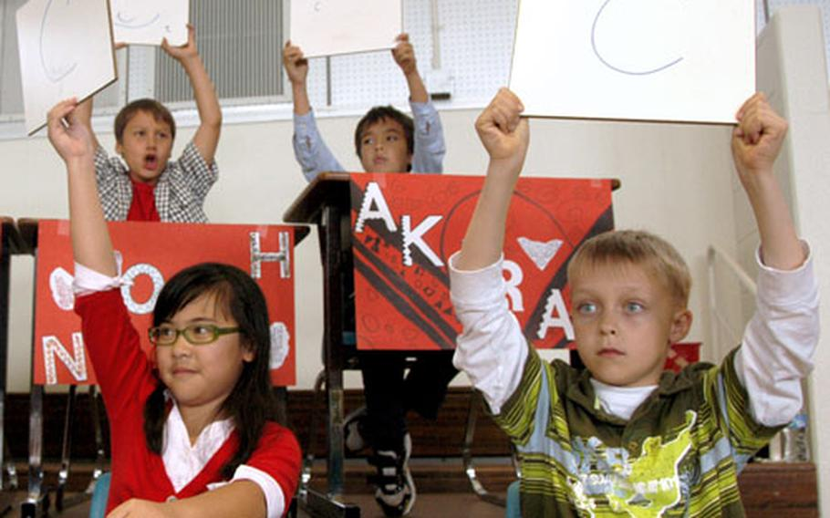 """Members of the Firebird class hold up answers to a quiz question Thursday during a game of """"Are you smarter than a Firebird?"""" at Amelia Earhart Intermediate School at Kadena Air Base on Okinawa."""