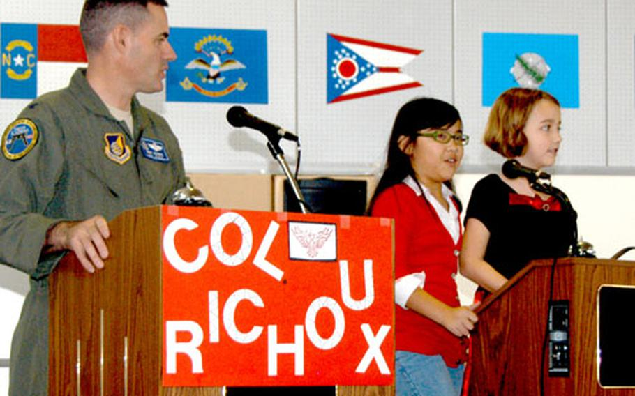 """Air Force Col. Lenny Richoux, left, vice commander of the 18th Wing at Kadena Air Base, Okinawa, is introduced to two student helpers, Katrina Stebbins, a fourth-grader, center, and third-grader Rachael Foley, during a round of """"Are you smarter than a Firebird?"""""""