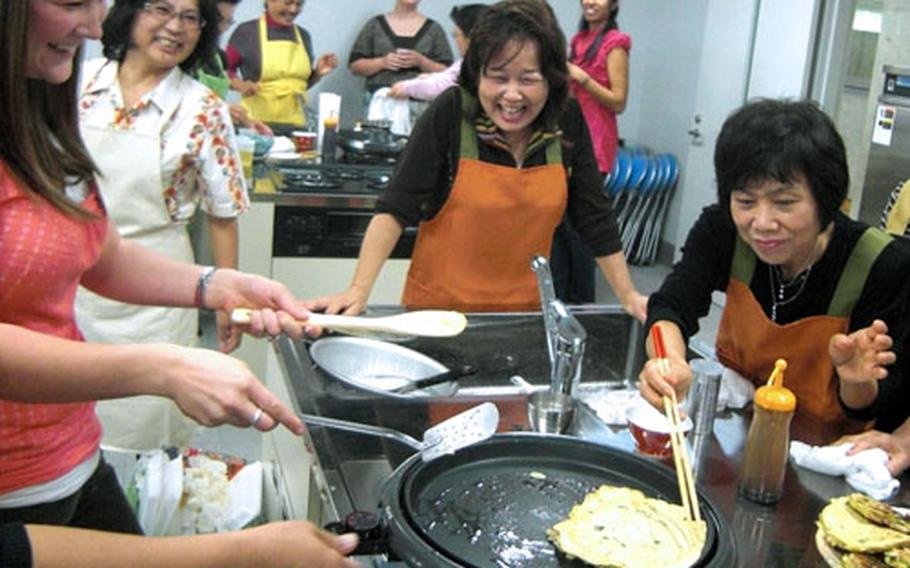 Krystal Roebuck, chairman of Okinawa Enlisted Spouse Club at Kadena Air Base, left, gets a helping hand Saturday from Sachiko Yamada, right, in flipping over an Okonomiyaki pancake on the hot plate. A cooking exchange wass part of the Bilateral Friendship Day at Kadena Town, Okinawa.