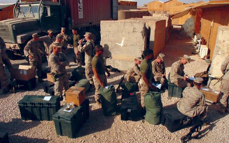 Marines at Camp Eagle, an outpost in Ramadi, wait in line to send mail home. The Marines are leaving in April, and many sent their extra gear home so they wouldn't have to carry it with them on the trip home. A traveling post office goes to Camp Eagle, population 140, about once every two weeks.