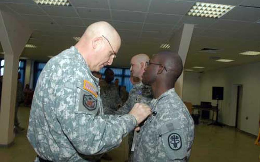 Lt. Gen. Kenneth Hunzeker pins a medal on Pfc. Derraivius Strawder at a ceremony held in Baumholder. Strawder was awarded the Army Commendation Medal with Valor for his actions in a firefight in Baghdad on June 23.