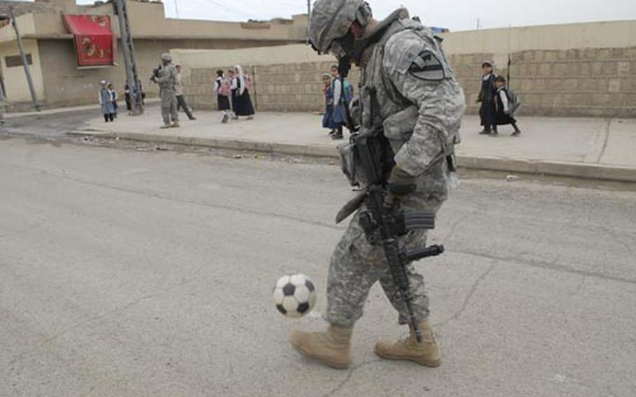First Lt. Alexander Mullin juggles a soccer ball in the streets of Mosul. Mullin has an invitation to join the U.S. National Team Handball squad and potentially play in the 2012 Olympics but he is trying to figure out if he can join the team while staying on as his platoon's leader in Iraq the rest of his tour.