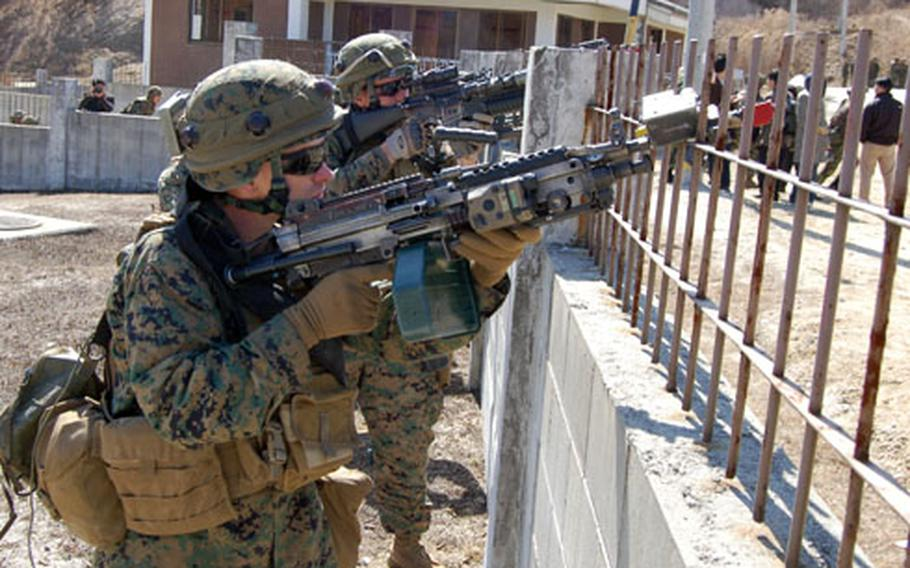 Marines from L Company, 3rd Battalion, 5th Marine Regiment, place suppressive fire on a building while members of their unit practice clearing rooms Tuesday at Rodriguez Range.