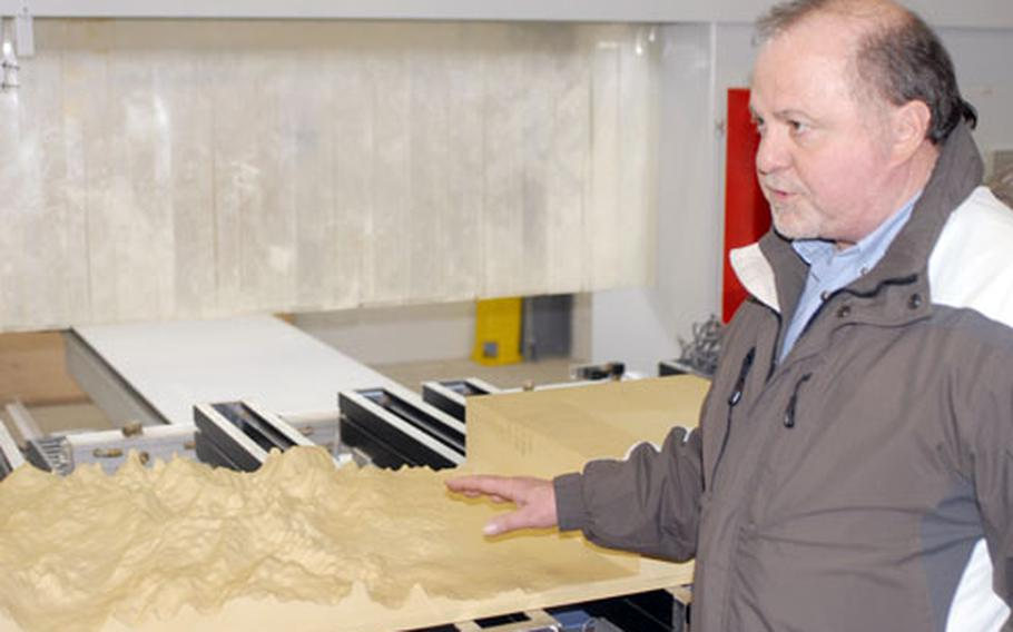 Training Aids Production Center chief John Krollpfeiffer demonstrates a machine that makes three-dimensional terrain models.
