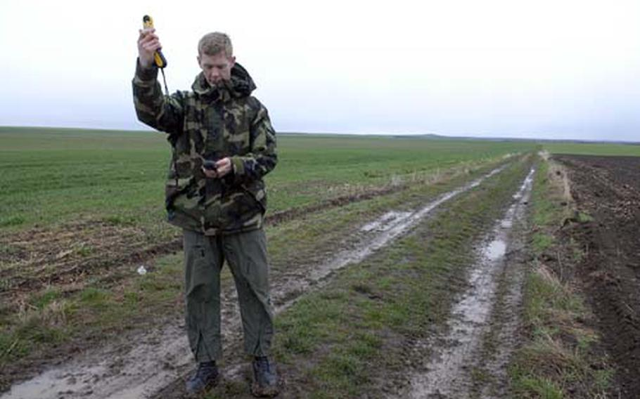 First Lt. Ryan Taylor, a C-130E co-pilot with the 37th Airlift Squadron, checks wind speed and direction in a farmer's field in Bulgaria. The field was the site of a sandbag airdrop by a C-130E and C-130J aircraft.