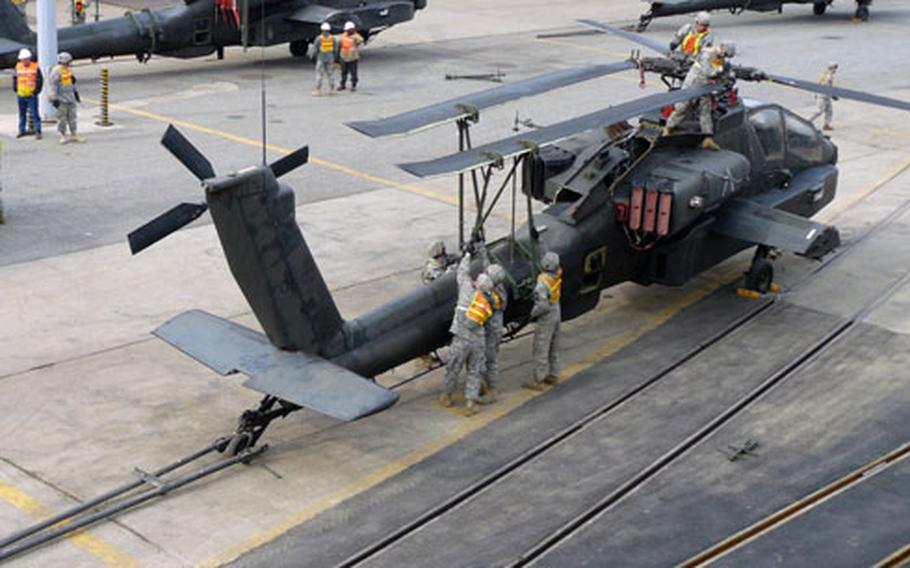 Soldiers of the Army's 602nd Aviation Support Battalion prepare AH-64D Apache Longbow attack helicopters at Pier 8 in Busan, South Korea, on Monday for shipment to the United States later this month.