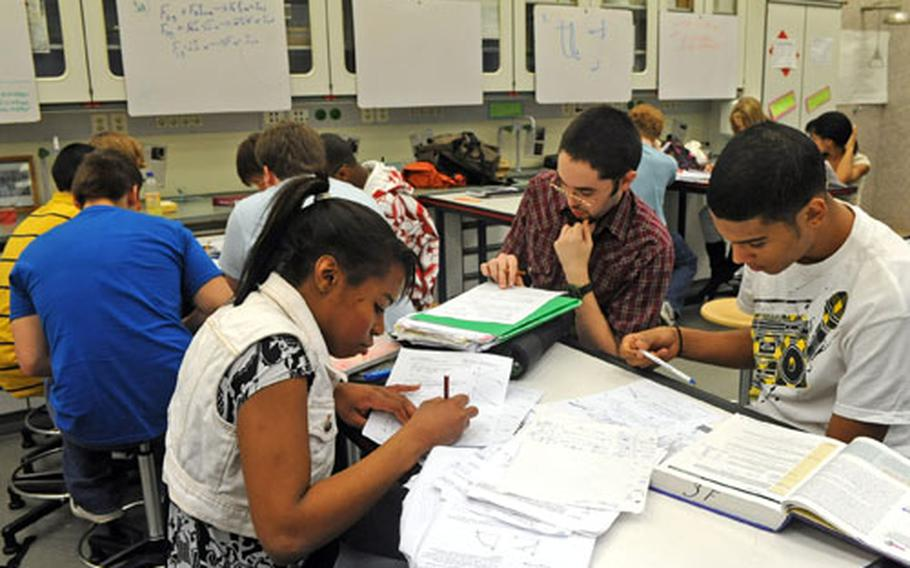 Natalie Thomas, Ryan Jarnagin and Dimitri Nzerem, foreground from left, work out a problem during a physics class at Kaiserslautern High School.