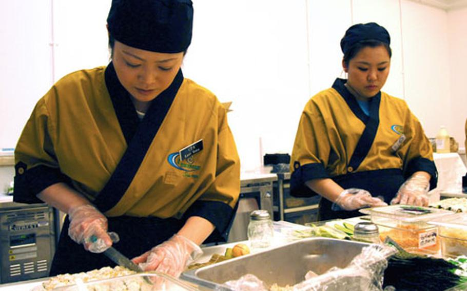Kaori Mukai, left, and Maki Seito, prepare sushi Saturday prior to the grand opening of the new sushi bar in the Misawa Air Base, Japan, Defense Commissary Agency store.