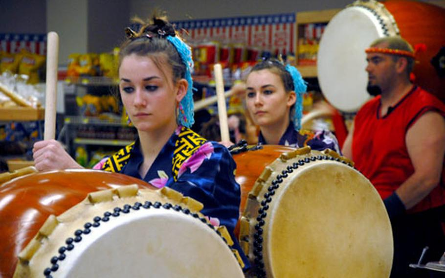 From left: Jacquelin Steel, her twin sister, Stephanie, and David Wray, members of the Dragon-Eagle Taiko drum team, perform Saturday at the grand opening of the sushi bar.