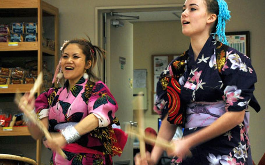 Kazuko Igarashi, left, and 13-year-old Jacquelin Steel, members of the Dragon-Eagle Taiko drum team, perform at the grand opening.