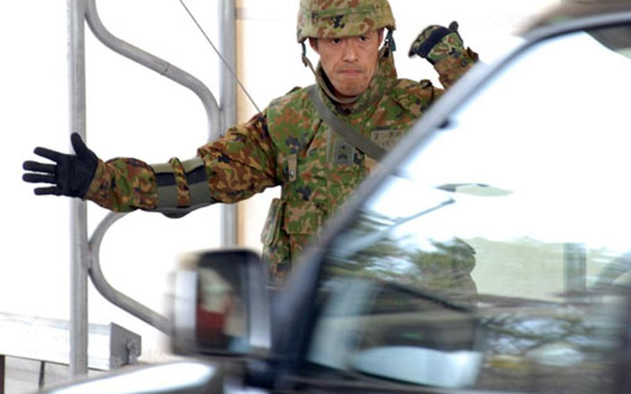 A member of the Japan Ground Self-Defense Force 9th Division, 5th Infantry Regiment, waves a vehicle into an inspection point Friday during a force-protection exercise on Misawa Air Base, Japan.